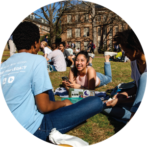 Three students study and laugh together in the main quad at UNC.